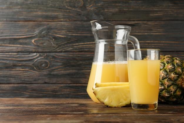 Ananas, brocca di vetro e vetro con succo su fondo di legno, spazio per testo