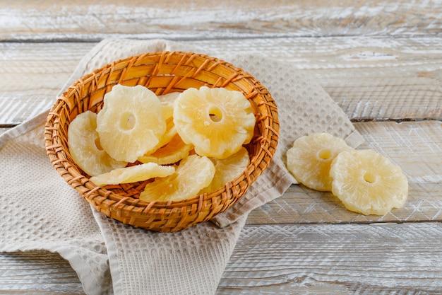 Ananas candito in un cestino sulla superficie dell'asciugamano di cucina e di legno