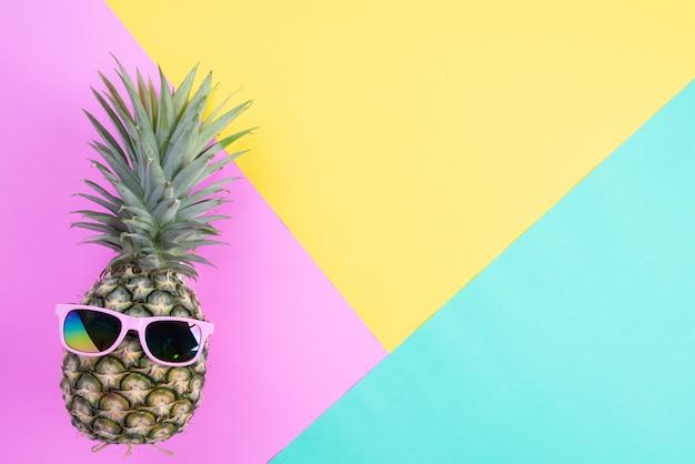 Ananas con occhiali da sole rosa su sfondo rosa, verde e giallo
