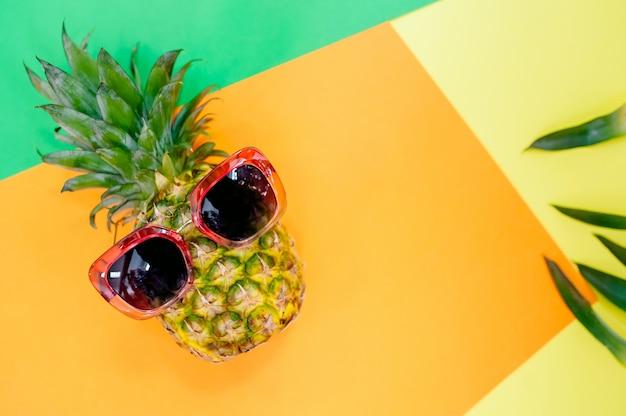 Ananas con occhiali e copia spazio. le intere ananas fresche fruttificano in occhiali dorati su fondo variopinto.