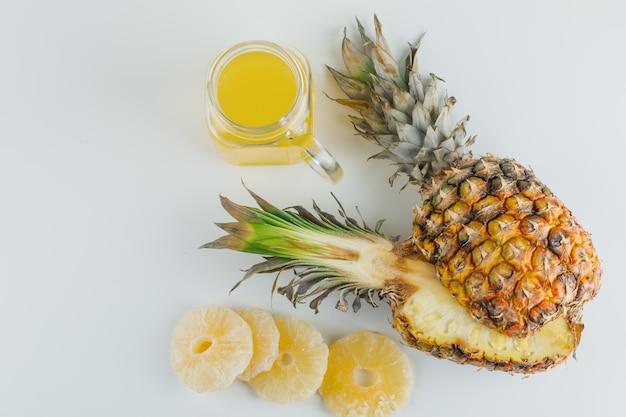Ananas con succo e anelli canditi su superficie bianca