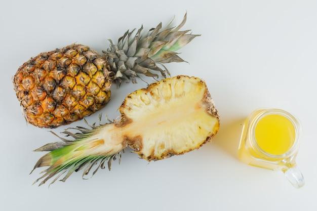 Ananas con succo su superficie bianca