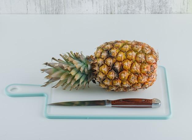 Ananas con tagliere e coltello