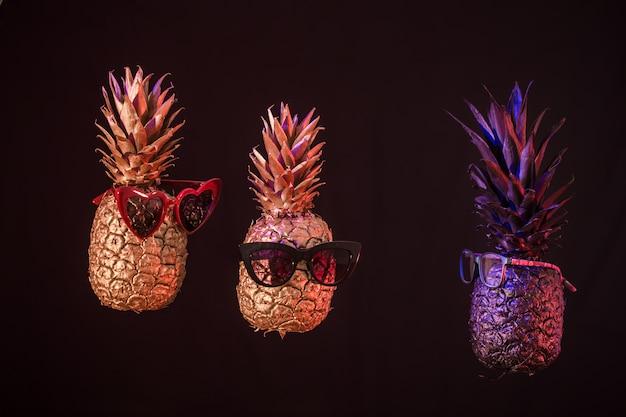 Ananas creativi con gli occhiali su uno sfondo nero