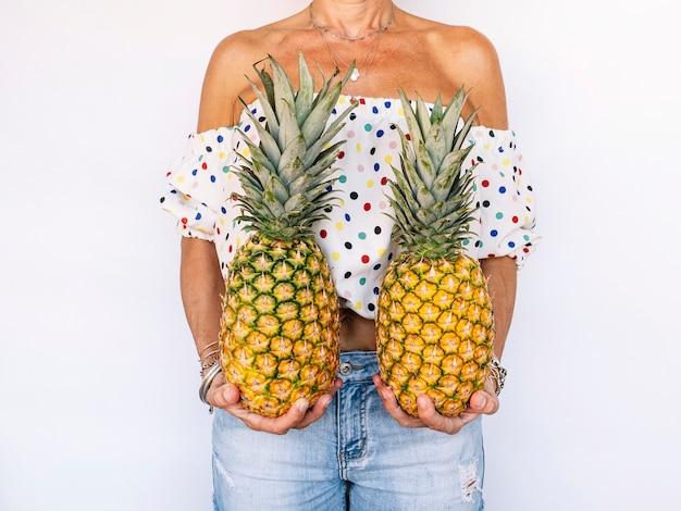 Ananas della tenuta della donna contro la parete bianca