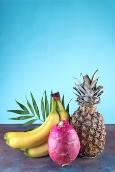 Ananas di frutta tropicale assortiti, mango, frutto del drago, su fondo di pietra. gruppo di frutti tropicali esotici. vegetariano concetto sano