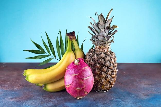Ananas di frutta tropicale assortiti, mango, frutto del drago, su fondo di pietra. gruppo di frutti tropicali esotici.