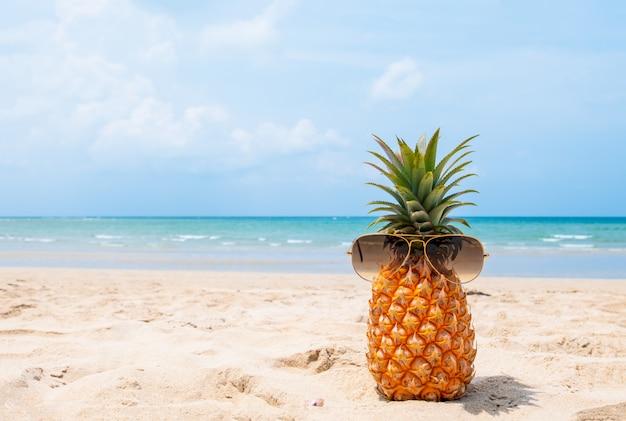 Ananas di hipster con occhiali da sole sulla spiaggia tropicale.