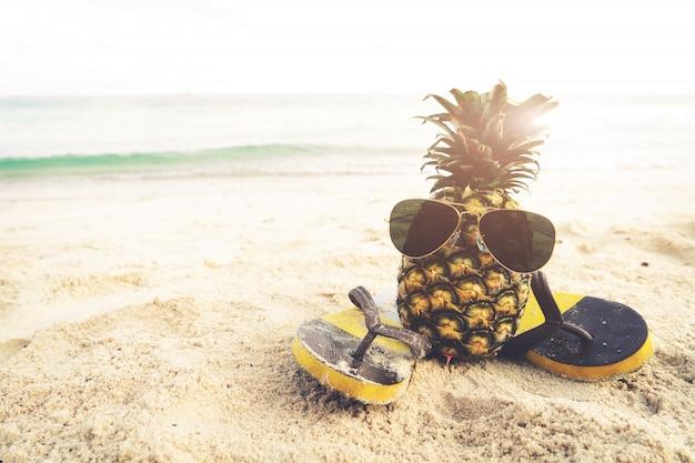 Ananas di hipster sulla spiaggia - moda in estate. effetto filtro dell'annata
