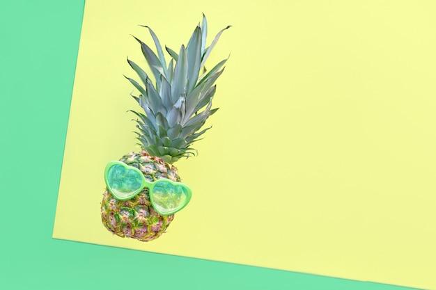 Ananas divertente in occhiali da sole a forma di cuore su fondo geometrico di carta diagonale in neo verde e giallo