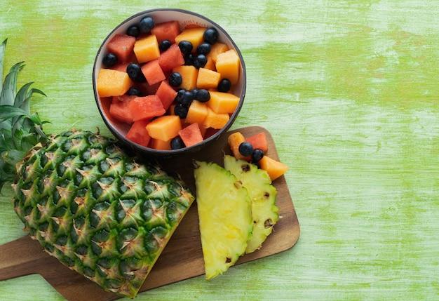 Ananas e ciotola affettati di frutti su fondo di legno verde