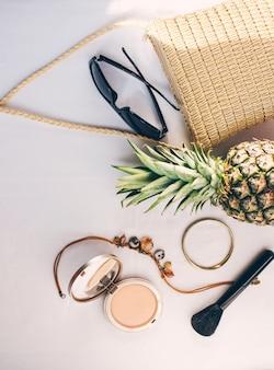 Ananas e cosmetici con sacchetto di vimini sono su un vestito di fondo chiaro per le donne