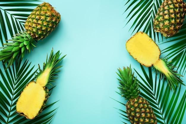 Ananas e foglie di palma tropicali sul fondo del turchese pastello duro. concetto di estate la disposizione piatta creativa con lo spazio della copia.