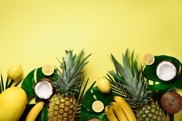 Ananas esotico, noci di cocco mature, banana, melone, limone, palma tropicale e foglie verdi di monstera