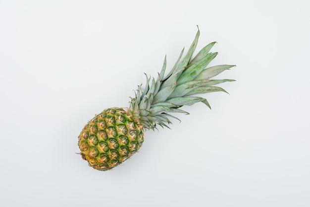 Ananas fresco succoso su gradiente bianco, piatto disteso.