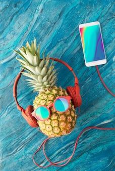 Ananas in occhiali da sole e auricolari con smart phone sulla parete di arte liquida acrilica turchese