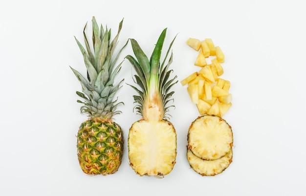 Ananas intero, metà e fette vista dall'alto su un bianco