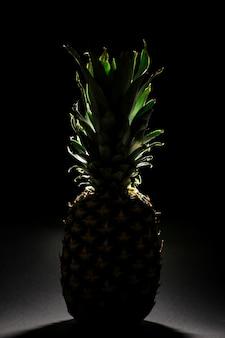 Ananas intero su un colore scuro. ananas maturo con un contorno luminoso.