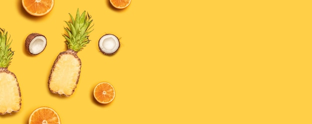 Ananas, limoni, arance e noci di cocco su uno sfondo giallo.