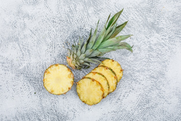 Ananas maturo affettato sulla superficie del grunge, vista superiore.