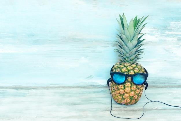 Ananas maturo con occhiali da sole a specchio blu e cuffie davanti a uno sfondo rustico in legno blu.