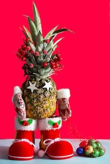 Ananas natalizio in stivali da babbo natale, muffole invernali e un sacchetto di caramelle color cioccolato