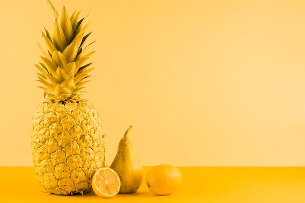 Ananas; pera e limone dimezzato su sfondo giallo