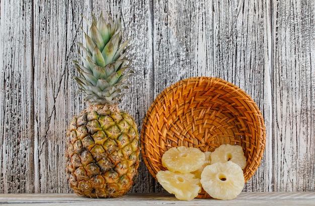 Ananas secchi con ananas fresco in un cestino su superficie di legno