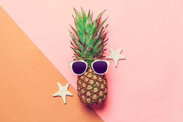 Ananas su carta colorata con gli occhiali