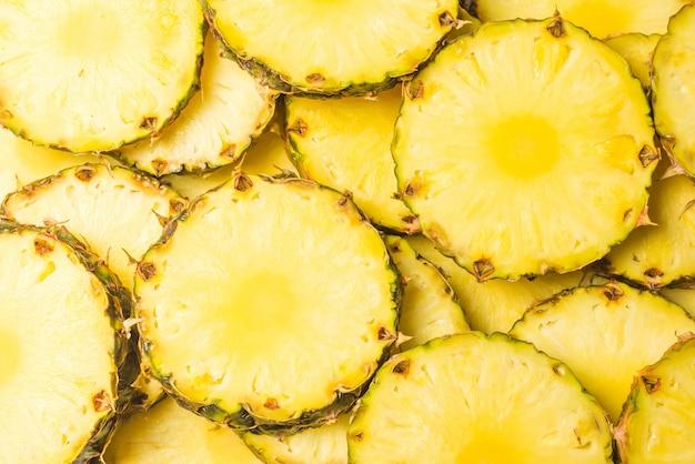Ananas succose fette di sfondo giallo. vista dall'alto.