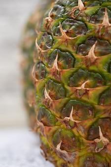Ananas succosi maturi sulla superficie di lerciume, primo piano.