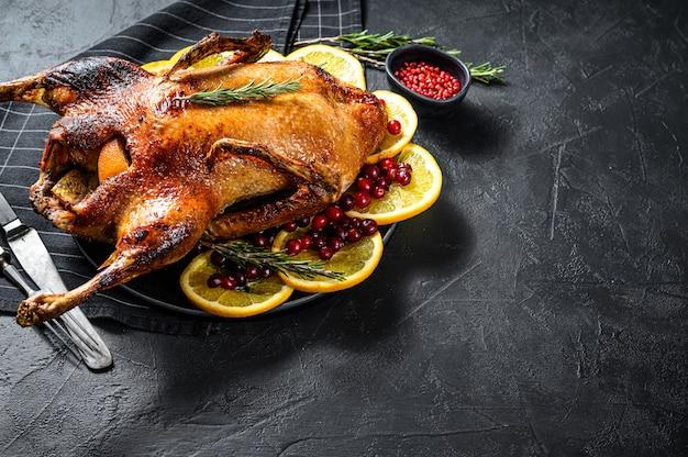 Anatra al forno ripiena di arance e rosmarina. tavolo festivo vista dall'alto. spazio per il testo