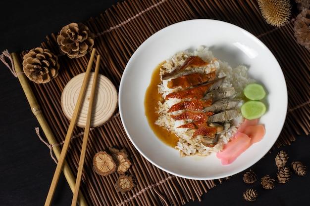 Anatra arrostita su riso con la bacchette in piatto bianco, alimento tailandese della via.