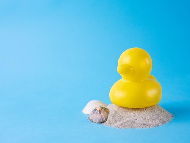 Anatra di gomma gialla sulla sabbia con conchiglie