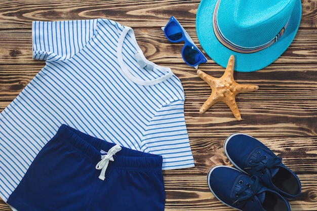 Ancora piatto di abbigliamento per bambini. armadio per bambini. vestiti da spiaggia e vacanze per un bambino. sfondo di legno