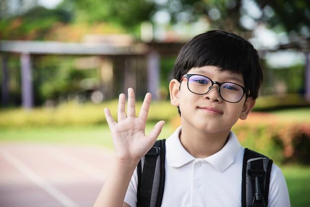 Andare a scuola felice del giovane ragazzo asiatico della tailandia