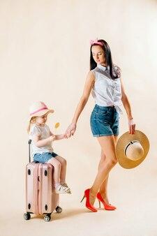 Andare all'avventura. famiglia felice che prepara per il viaggio. mamma e figlia stanno facendo le valigie per il viaggio.