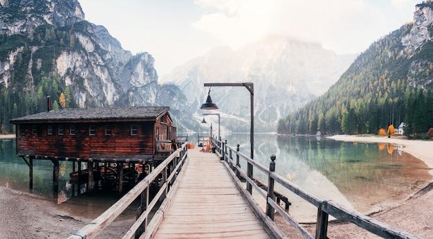 Andare in acqua. buon paesaggio con le montagne. luogo turistico con edificio in legno e molo