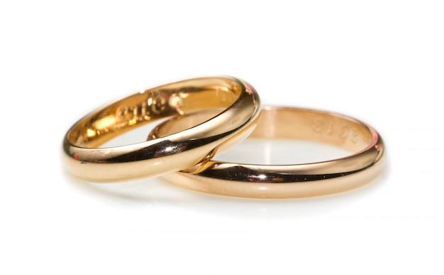 Anelli d'oro isolati su sfondo bianco