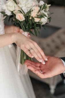 Anelli della sposa e dello sposo sullo sfondo del bouquet