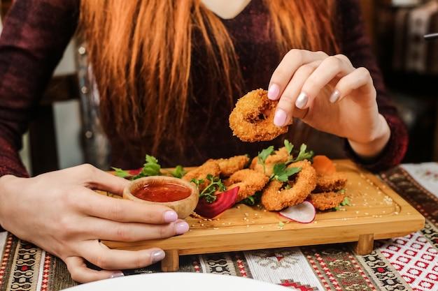 Anelli di calamari fritti con ravanello, prezzemolo, sesamo e salsa di peperoncino dolce