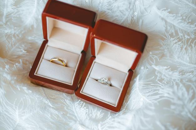 Anelli di diamante delle coppie di nozze dentro le scatole rosse.