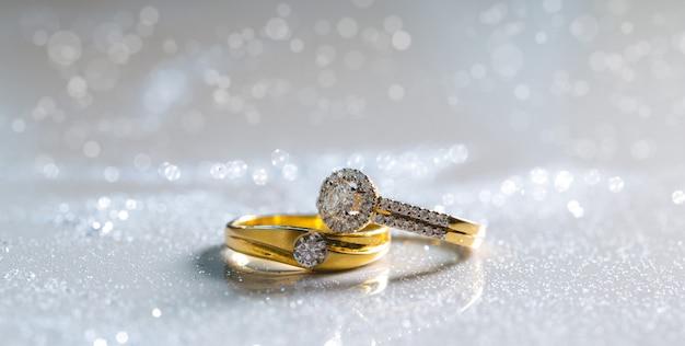 Anelli di diamante delle coppie di nozze disposti su terra bianca. ci sono polvere di diamante.