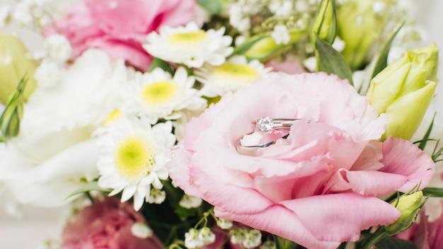 Anelli di diamante di nozze sul mazzo di fiori
