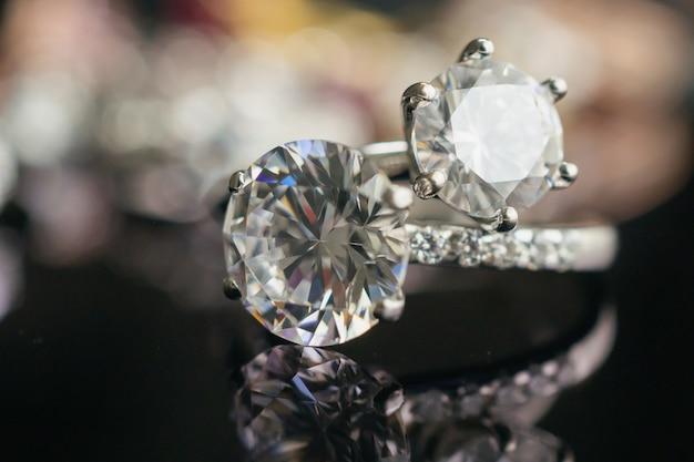 Anelli di diamanti gioielli su superficie nera con riflessione