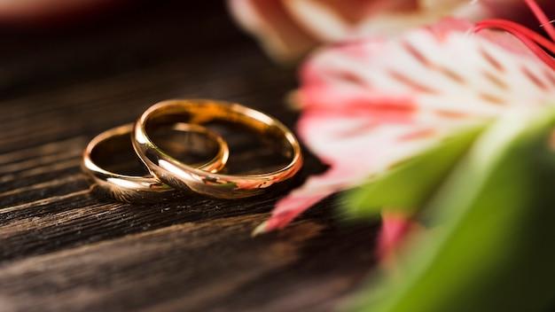 Anelli di fidanzamento del primo piano accanto ai fiori