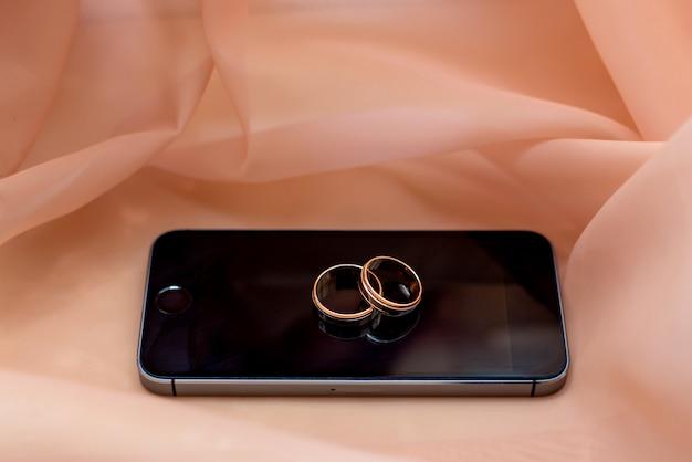 Anelli di nozze d'oro al telefono. fidanzamento sposato