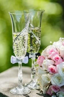 Anelli di nozze d'oro con rose e bicchieri di champagne