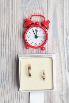 Anelli di nozze d'oro in confezione regalo con un orologio rosso. vista dall'alto.