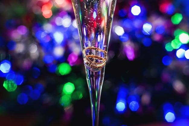 Anelli di nozze d'oro in un bicchiere di champagne su un luminoso colorato